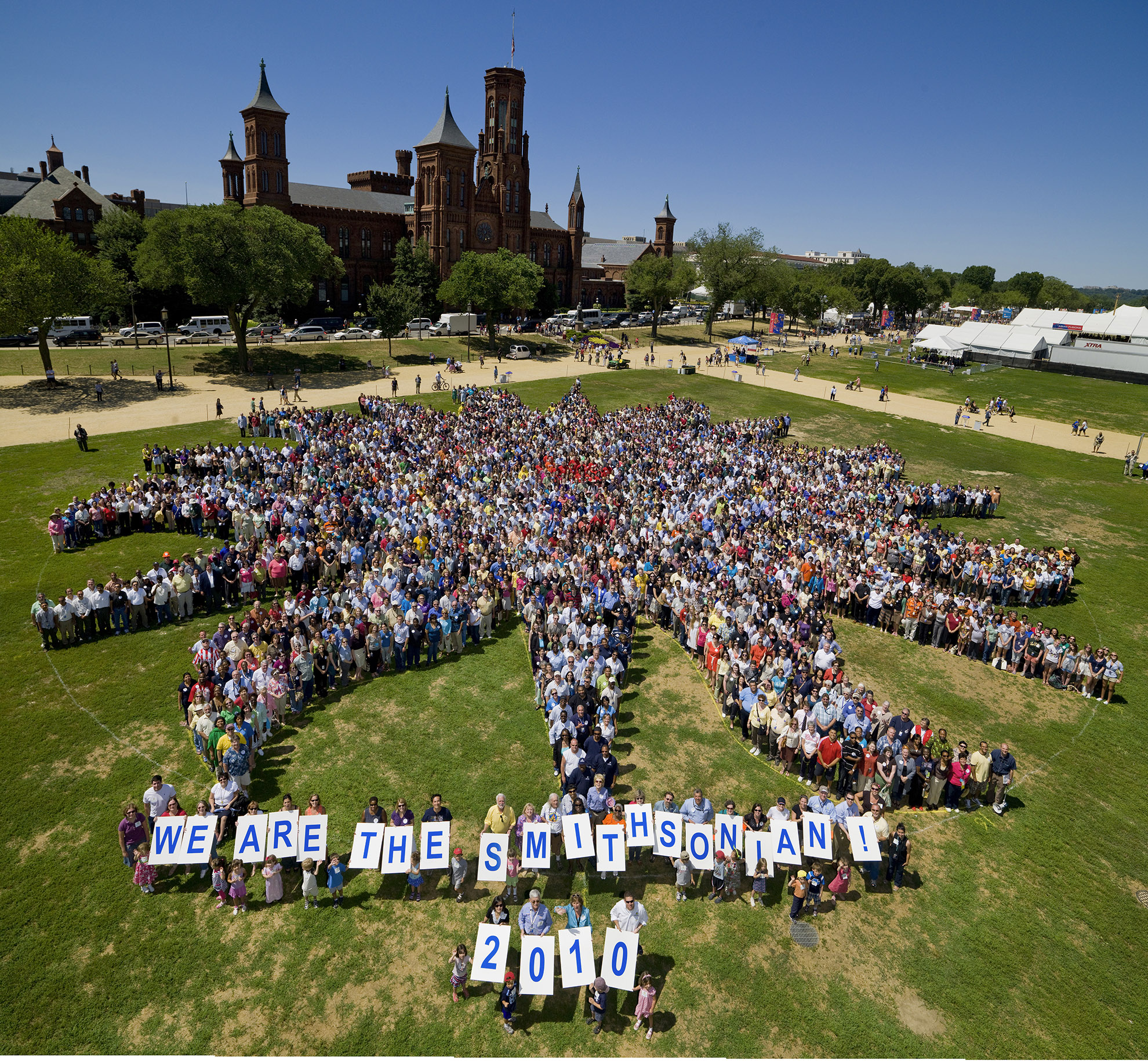 Standing in the shape of the Smithsonian Institution sunburst, close to 4,000 Smithsonian staff, interns, fellows and volunteers gathered on the National Mall in front of the Smithsonian Castle on Thursday, July 1, for this group portrait. This was the first-ever attempt to gather the employees and others for a group shot in the Smithsonian's 164-year history and was the largest gathering of Smithsonian employees, fellows, interns, volunteers and retirees to date. The photo was organized by the Smithsonian Community Committee and was taken during the Smithsonian Staff Picnic, held annually on the National Mall.  Photo: Dane Penland, Smithsonian Institution